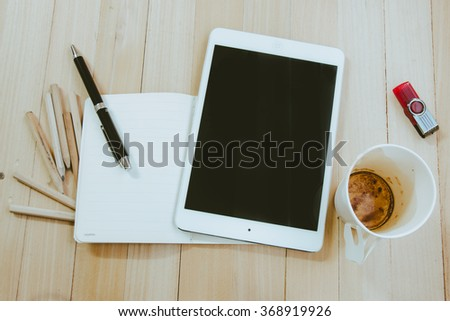Office supplies, empty coffee cup, and tablet on the wood table background, top view