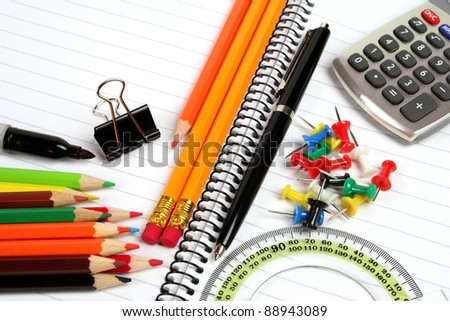 Office supplies on notebook background