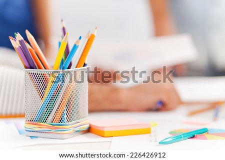 Office supply. Close-up of office supply laying on the table while people working in the background - stock photo
