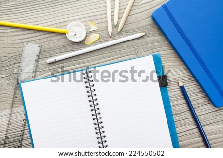 Office supply collection - sharpener, pencils, ball pen, notebooks and ruler - on brown wooden table. - stock photo