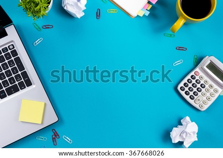 Office table desk with set of colorful supplies, white blank note pad, cup, pen, pc, crumpled paper, flower on blue background. Top view and copy space for text - stock photo