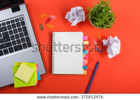 Office table desk with set of colorful supplies, white blank note pad, cup, pen, pc, crumpled paper, flower on red background. Top view and copy space for text - stock photo