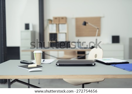 Office Table of a Businessman with Office Supplies, Laptop Computer, Mobile Phone and a Cup of Coffee on Top. - stock photo