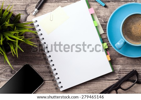 Office table with a coffee cup, a blank notepad and a plant - stock photo