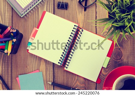 Office table with flower, blank notepad and coffee cup. View from above with copy space. Toned - stock photo