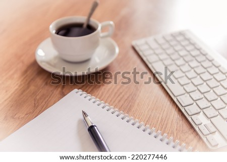 Office table with notepad, computer keyboard and coffee cup  and pen. Instant photo split toning color effect - stock photo