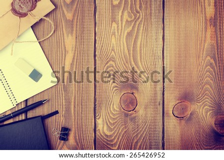 Office table with notepad, vintage envelope and supplies. View from above with copy space. Toned - stock photo