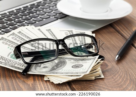 Office table with pc, coffee cup and glasses over money cash closeup - stock photo