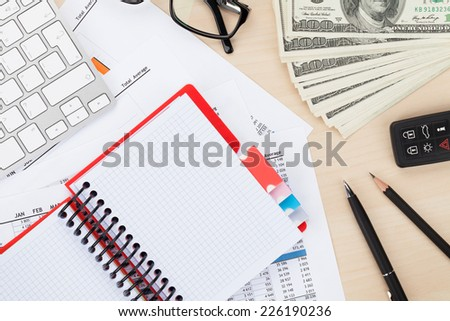 Office table with pc, supplies and money cash. View from above with notepad for copy space - stock photo