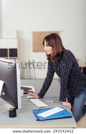 Office Woman Browsing Something at her Computer on Top of her Desk While in Standing Position.
