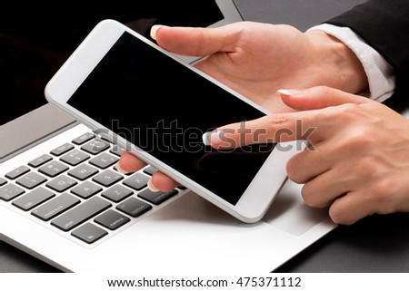 Office woman is holding the smart phone with one hand and pointing on it with another one