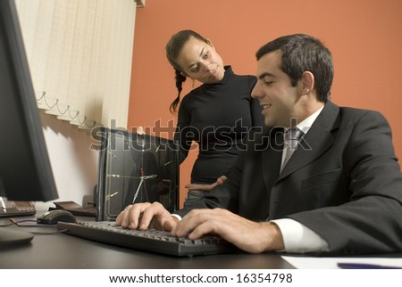 Office woman shows a businessman a giant clock while he types on his computer. Horizontally framed photo.