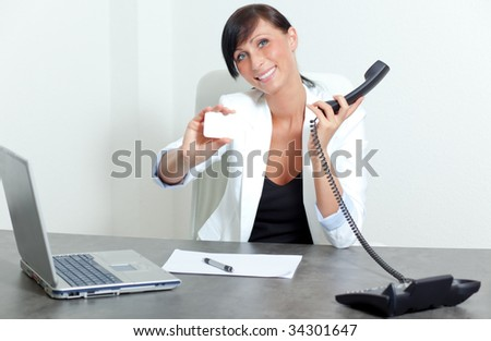 Office woman sitting and holding blank businesscard smiling on table and telephone