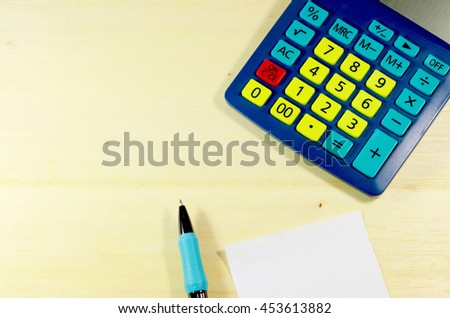Office wooden table with notepaper, pen and colorful calculator. View from above with copy space (Top view). - stock photo
