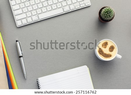 Office work space on grey desk with cactus and cappuccino. From above view on grey wooden desk with well organized office supplies and mug with cappuccino with chocolate smiley on the surface. - stock photo