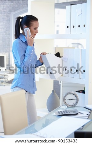 Office worker girl on mobile phone call standing at shelf, checking folders.? - stock photo