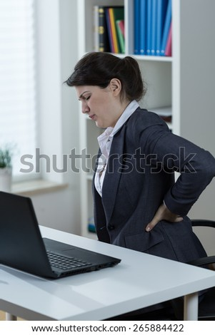 Office worker having backache caused by sedentary work - stock photo