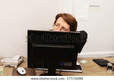 office worker hiding behind monitor - stock photo