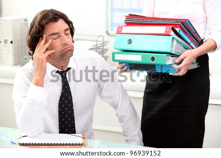 Office worker overwhelmed by load of work - stock photo