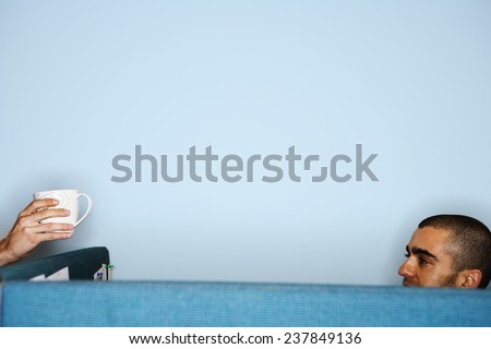 Office Worker Passing Mug - stock photo