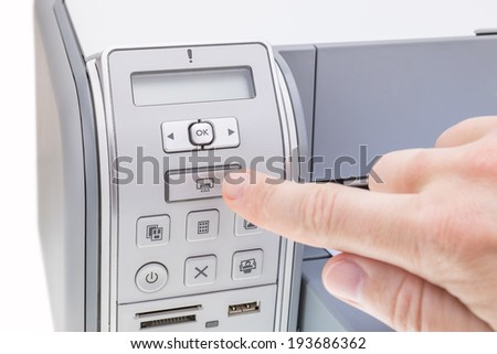 Office worker presses the button the printer. Close-up. - stock photo