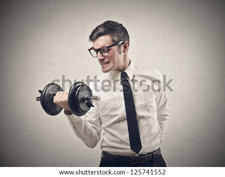 Office worker raising a dumbbell - stock photo