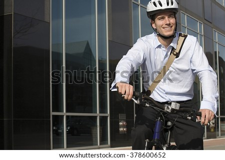 Office worker riding bicycle - stock photo