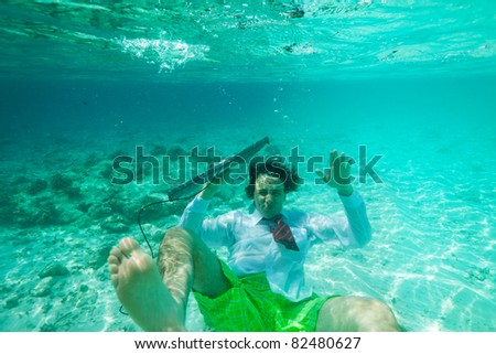 Office worker sinking - man in formal clothes with keyboard underwater shoot