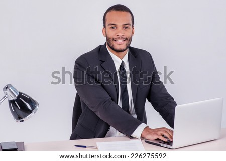 Office worker. Smiling African businessman sitting at the table and typing a business plan on a laptop while a businessman sitting at a desk and smiling at the camera isolated on a gray background - stock photo