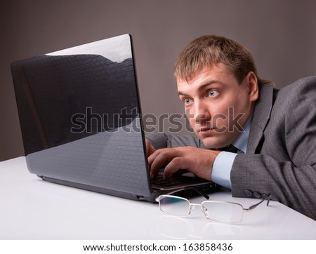 Office worker stares at the monitor with surprise - stock photo