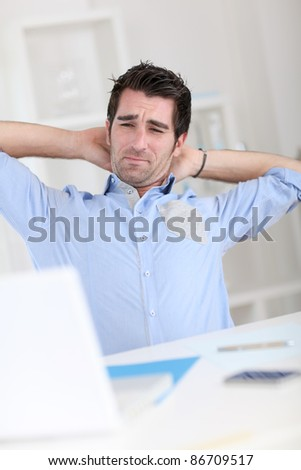 Office worker stretching arms at work - stock photo