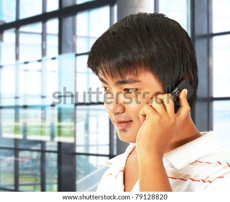 Office Worker Talking On The Phone In Front Of Many Windows - stock photo