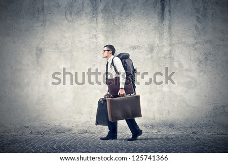 Office worker with a travel backpack and two briefcases - stock photo