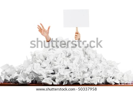 Office worker with blank sign buried in pile of screwed up papers, white studio background.