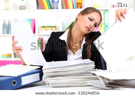 office worker with documents in her workplace - stock photo