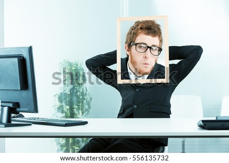 office worker with his arms relaxed and a picture frame with a photo of another face with a envy expression