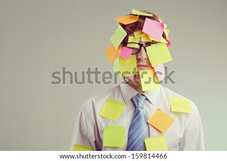 Office worker with post-its all over his face - stock photo