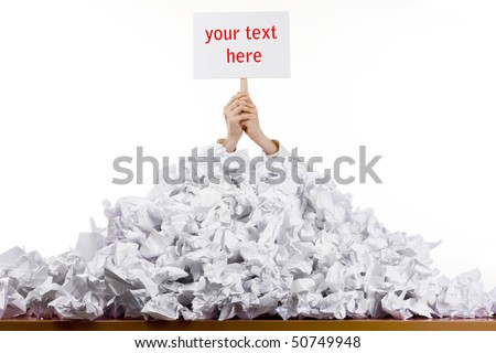 Office worker with sign buried in pile of screwed up papers, white studio background