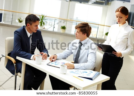 Office workers discussing financial statistics in office