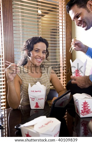 Office workers eating Chinese takeout food in boardroom while working on laptop - stock photo