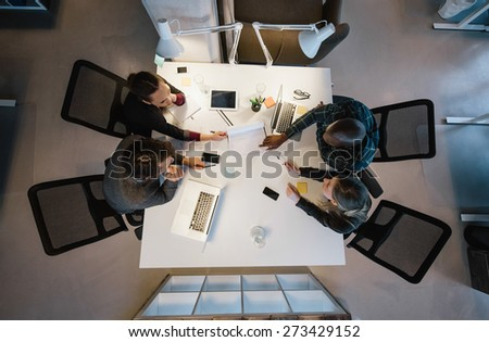 Office workers gather around a table to do research and implement new ideas. High angle view of multi-ethnic business people discussing in board room meeting - stock photo