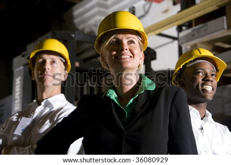 Office workers in storage warehouse wearing hard hats - stock photo