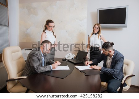 Office workers make the deal, sign the agreement on partnership and cooperation - stock photo