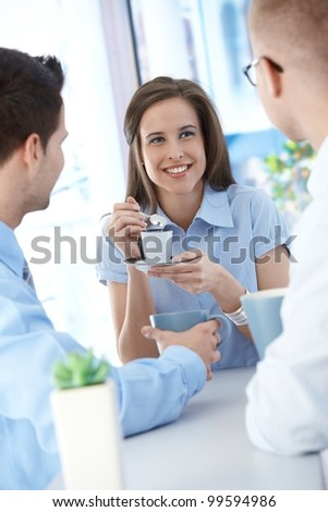 Office workers on coffee break, woman enjoying chatting to colleagues, smiling.