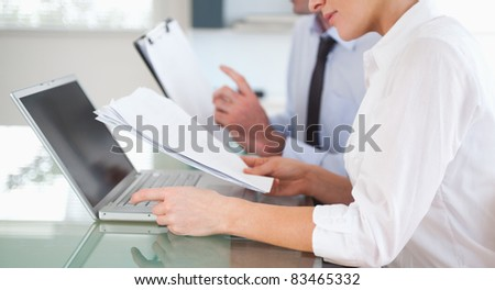 Office workers typing a report from blueprint documents in an office - stock photo