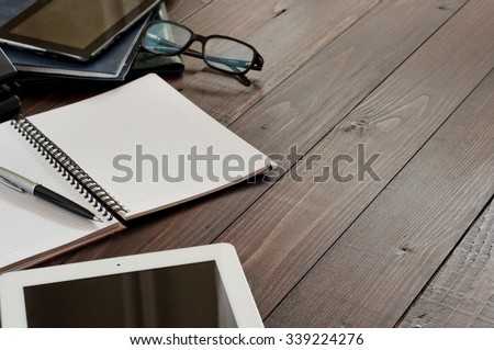 Office workplace. Open notebook, tablet computer, glasses, ballpoint and leather business folders on the office table. Top view. Free space for text. Copy space.  - stock photo