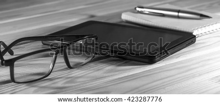 Office workplace/ Tablet PC, notebook and folder on the office desk, a cup of tea or a cup of coffee. View from above with copy space. Free space for text. Workplace/ black and white image - stock photo