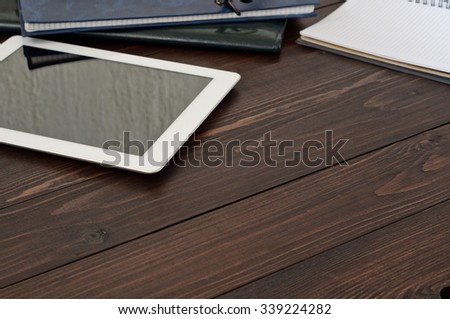 Office workplace. White tablet computer, a notebook and leather business folder on the office table. Top view with copy space. Free space for text - stock photo