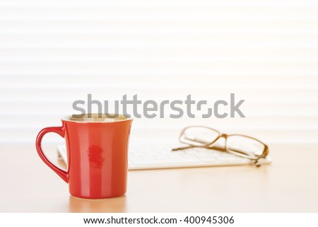 Office workplace with coffee and pc on wooden desk table in front of window with blinds - stock photo