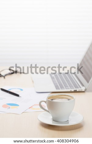 Office workplace with coffee cup, laptop and supplies on wood desk table in front of window with blinds. View with copy space - stock photo